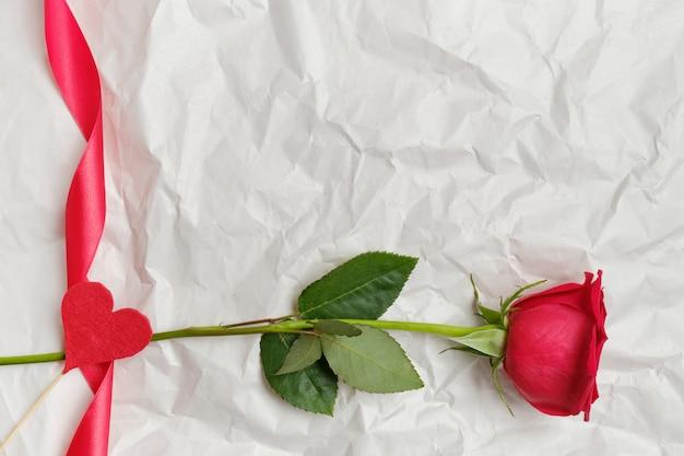 Schöne rote rose mit band und herz auf einem stock im hintergrund auf zerknittertem papier. draufsicht. speicherplatz kopieren.