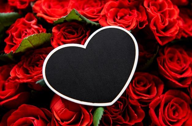Schöne rote rosen mit rahmenherz-valentinstaghintergrund