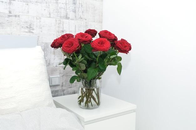 Schöne rote rosenstraußblumen auf weißem nachttisch durch bett mit weißem kissen auf hintergrund der grauen schmutzwand.