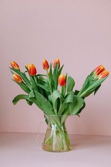 Schöne rote tulpen auf hellrosa hintergrund ein europäischer florist bereitet einen strauß tulpen für