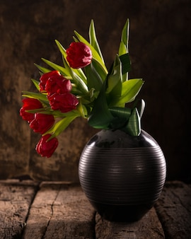 Schöne rote tulpen in der schwarzen vase auf einem hölzernen hintergrund