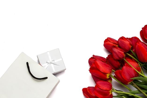 Schöne rote tulpen, verpackungspaket und geschenkbox auf einem weißen. draufsicht.