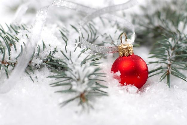 Schöne rote weihnachtskugeln mit tannenzweig und schnee auf weißem hintergrund