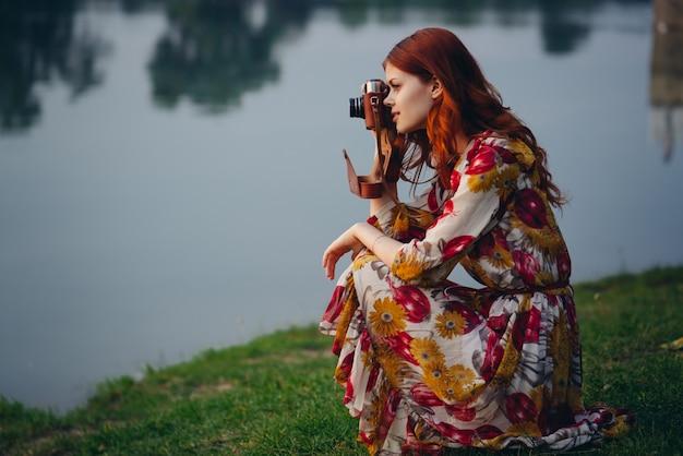 Schöne rothaarige fotografin mit einer alten kamera