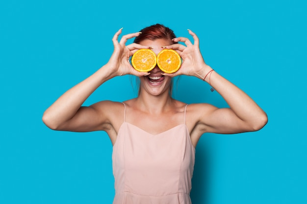 Schöne rothaarige frau bedeckt ihr auge mit geschnittenen zitronen, die auf einer blauen studiowand posieren
