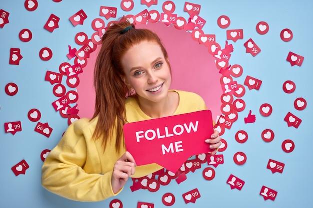 Schöne rothaarige frau, die follow me-zeichen hält, bittet, aktiver im internet zu sein, likes und nachrichten zu senden
