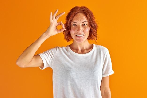 Schöne rothaarige frau, die ok zeichen mit hand und fingern lokalisiert über gelbem raum tut