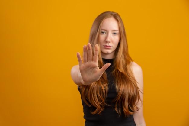 Schöne rothaarige frau, die über isolierte gelbe wand mit offener hand steht, die stoppschild mit ernstem und sicherem ausdruck, verteidigungsgeste tut. keine gewalt mehr gegen frauen. missbrauch.