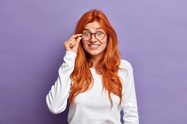 Schöne rothaarige frau hält hand am rand der brille blicke mit interesse hört etwas unglaubliches trägt weißen freizeitpullover.