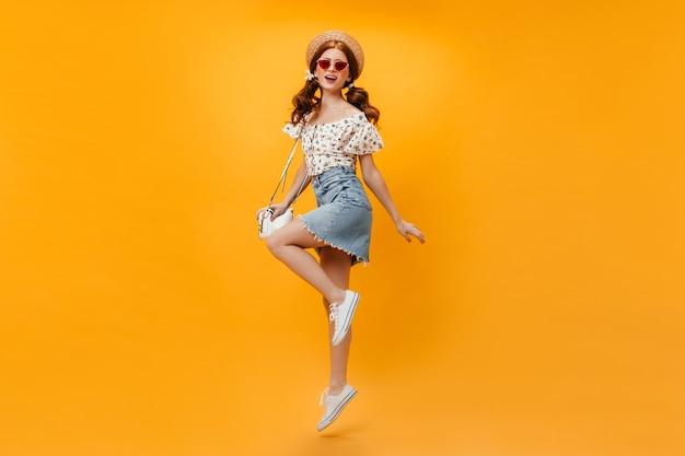 Schöne rothaarige frau im sommer-denim-outfit und im strohhut, die weiße tasche halten und auf orange hintergrund springen.