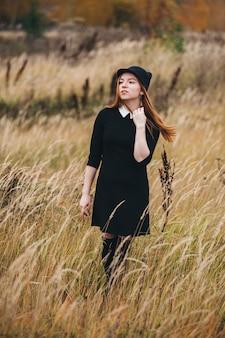 Schöne rothaarige frau in einem schwarzen kleid geht auf ein herbstfeld.