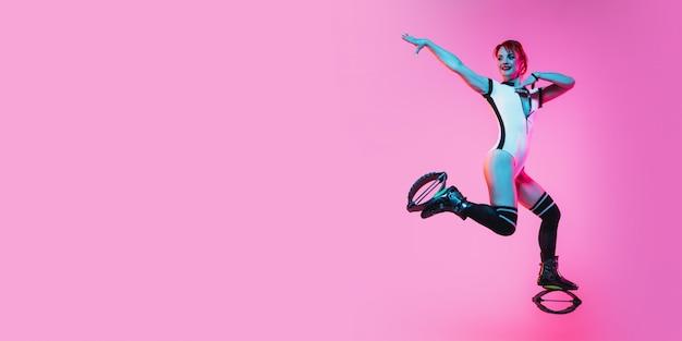 Schöne rothaarige frau in einer roten sportbekleidung, die in einem känguru springt, springt schuhe auf rosa studiohintergrund. flyer