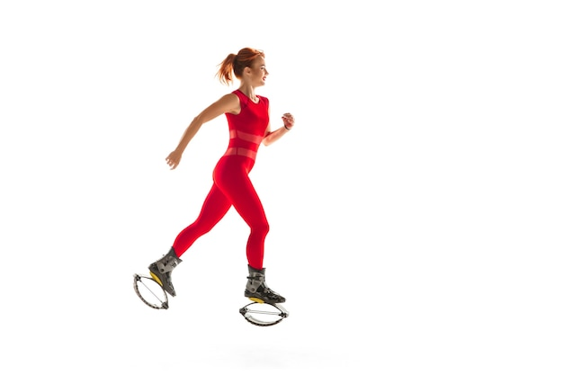 Schöne rothaarige frau in einer roten sportbekleidung, die in einem kangoo springt, springt schuhe einzeln auf weißem studiohintergrund. hochspringen, aktive bewegung, action, fitness und wellness. fit weibliches modell.