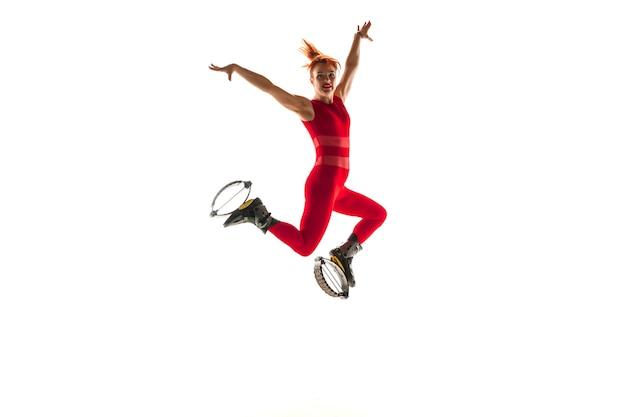 Schöne rothaarige frau in einer roten sportbekleidung, die in einem kangoo springt, springt schuhe isoliert auf weißem studio
