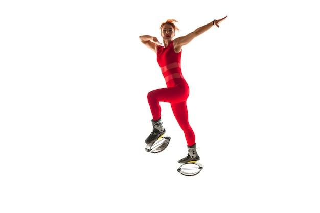 Schöne rothaarige frau in einer roten sportkleidung, die in ein känguru springt