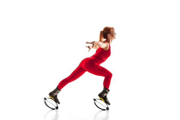 Schöne rothaarige frau in einer roten sportkleidung, die in einem kangoo springt, springt schuhe