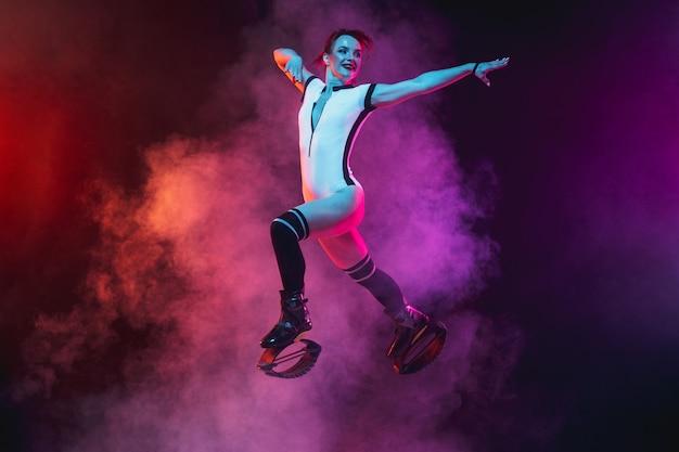 Schöne rothaarige frau in einer weißen sportbekleidung, die in einem kangoo springt, springt schuhe isoliert auf farbverlauf