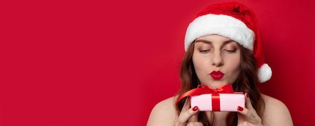 Schöne rothaarige frau in sankt-hut, der die kamera durchbrennt einen kuss mit der hand auf luft betrachtet und präsentkarton mit satinbandbogen auf rot hält