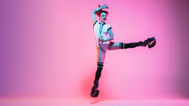 Schöne rothaarige frau in sportbekleidung, die in einem kangoo springt, springt schuhe einzeln auf lila-rosa farbverlauf studiohintergrund im neonlicht. aktive bewegung, action, fitness und wellness. fit weibliches modell.