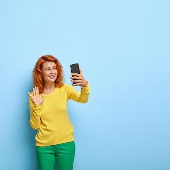 Schöne rothaarige frau macht videoanruf, spricht mit verwandten, winkt vor der kamera, hat ein freundliches lächeln