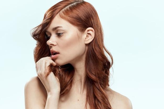 Schöne rothaarige frau mit lockigem haar. haarpflege, gesund und glänzend, ohne spliss
