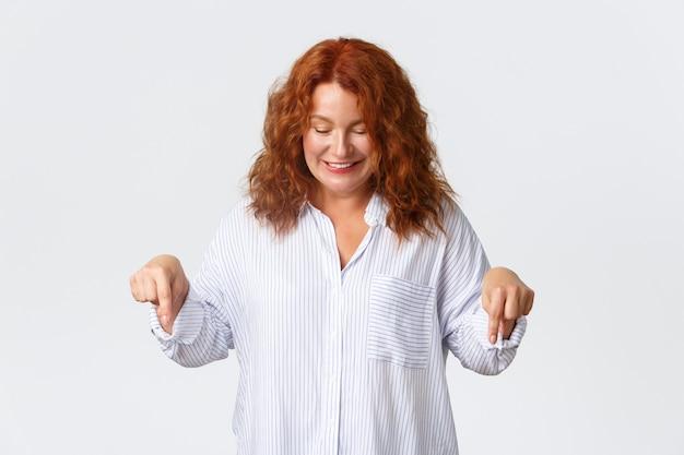 Schöne rothaarige frau mittleren alters im hemd, das finger mit glücklichem, niedlichem lächeln schaut und zeigt