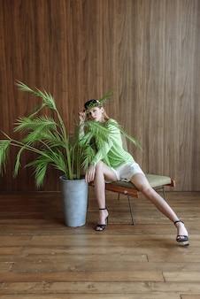 Schöne rothaarige frau posiert beim sitzen auf einem stuhl in einer neuen kleiderkollektion im studio