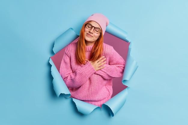 Schöne rothaarige frau schätzt etwas macht dankbarkeit geste schließt die augen und steht berührt neigt den kopf in rosa kleidung gekleidet.
