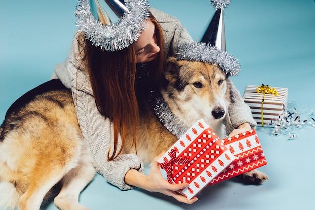 Schöne rothaarige frau sitzt mit ihrem hund auf dem boden und wartet auf das neue jahr 2018