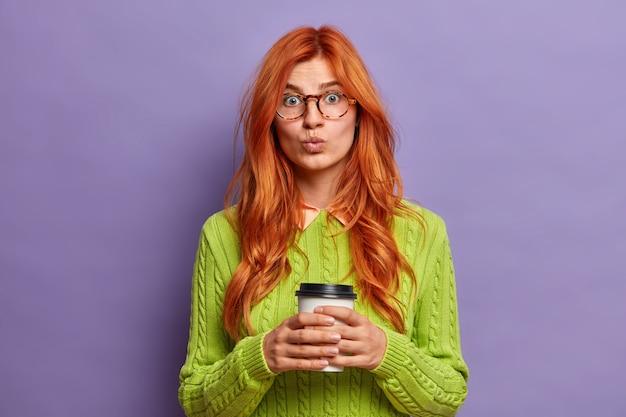 Schöne rothaarige junge frau hält die lippen rund und sieht überraschend hält einweg tasse kaffee genießt freizeit trägt grünen pullover.