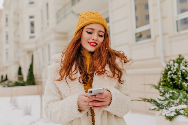 Schöne rothaarige mädchen sms-nachricht. außenfoto der interessierten jungen frau im mantel, der mit telefon im winter aufwirft.