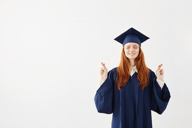 Schöne rothaarige weibliche absolventin beten.