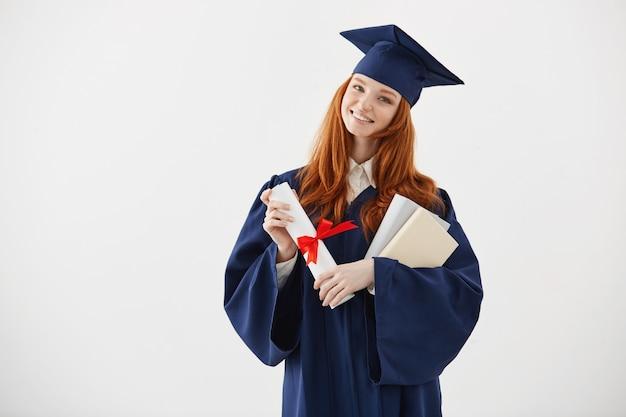 Schöne rothaarige weibliche absolventin, die bücher und diplom lächelnd hält.