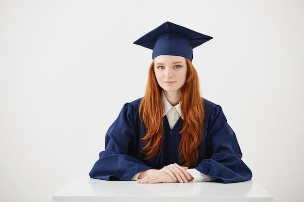 Schöne rothaarige weibliche absolventin lächelnd.