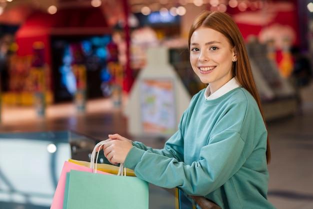 Schöne rothaarigedame, die einkaufstaschen hält