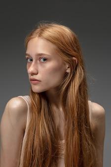 Schöne rothaarigefrau auf grauem studiohintergrund, mode