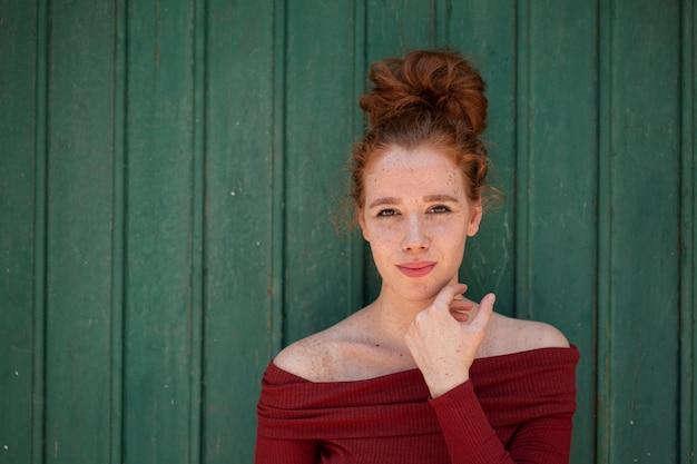 Schöne rothaarigefrau, die kamera betrachtet