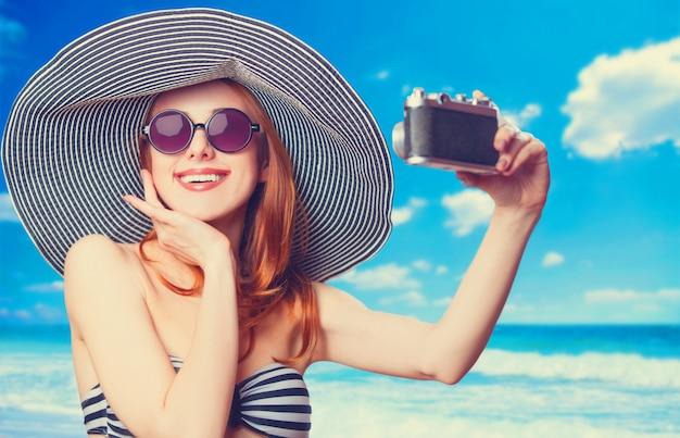 Schöne rothaarigefrau, die selfie auf einem strand macht.