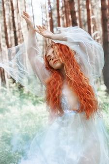 Schöne rothaarigefrauen-waldnymphe im blauen kleid