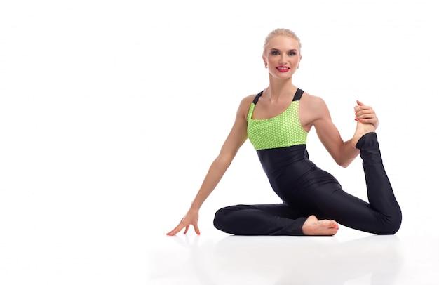 Schöne rotlippige frau in schmal geschnittenen sportoutfits, die im yoga sitzen