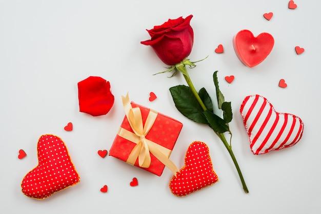 Schöne rotrosenblume mit herzen und geschenkbox