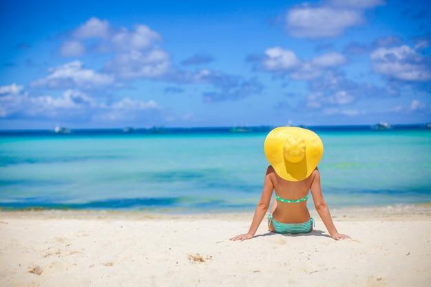 Schöne rückseite des modells im bikini und im hut, die sich hinsetzen.