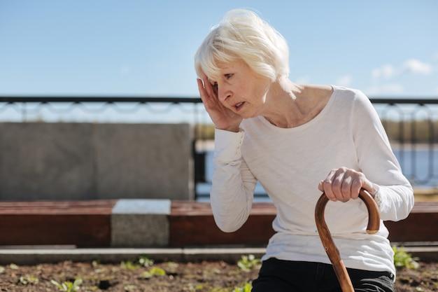 Schöne ruhige ältere frau, die sich auf eine bank setzt und unter kopfschmerzen leidet, während sie durch den park geht