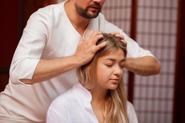 Schöne ruhige frau, die fröhlich lächelt, während der professionelle thailändische masseur ihren kopf massiert. attraktive frau, die kopfmassage in der thailändischen badekurortmitte empfängt. stressabbau, heilung, gesundheit
