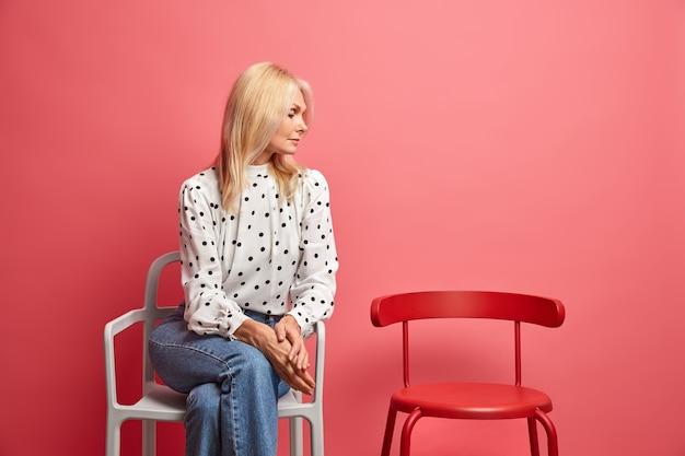 Schöne ruhige frau mittleren alters mit hellem haar sitzt allein und schaut auf leeren stuhl, der tief in gedanken ist, trägt modische gepunktete bluse und jeans fühlt sich einsam zu hause