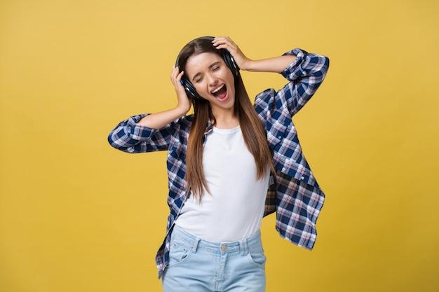 Schöne ruhige junge frau, die die musik im kopfhörer mit geschlossenen augen auf gelbem hintergrund hört. nahaufnahme