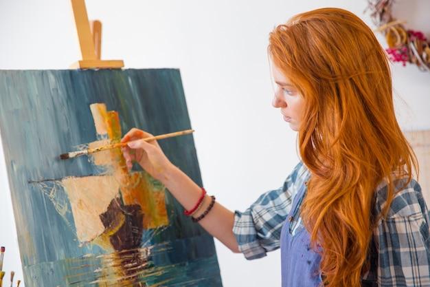 Schöne ruhige junge malerin mit langen roten haaren, die in der kunstwerkstatt ein bild auf leinwand malen