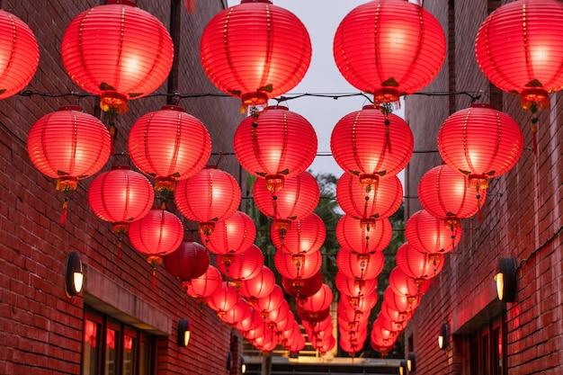 Schöne runde rote laterne, die an der alten traditionellen straße, konzept des chinesischen mondneujahrsfestes, nah oben hängt. das zugrunde liegende wort bedeutet segen.