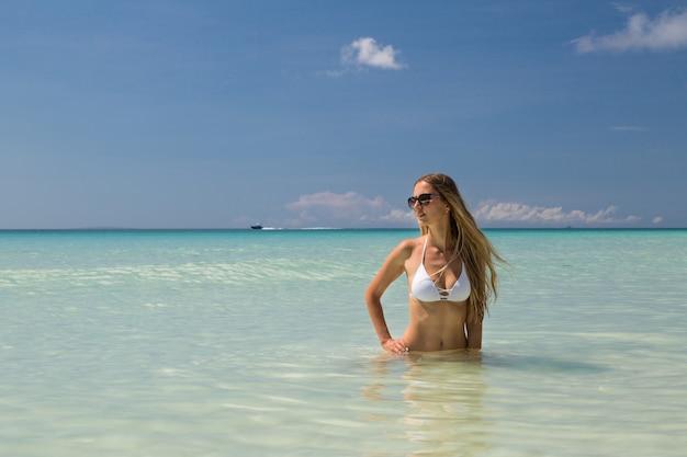 Schöne russische frau mit langen blonden haaren im weißen bikini am tropischen strand