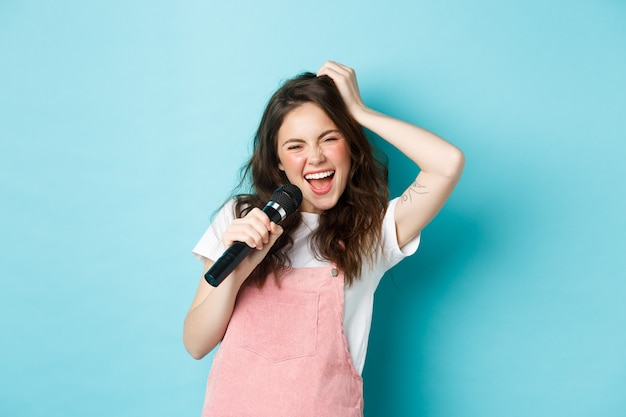 Schöne sängerin mit mikrofon, karaoke-singen im mikrofon, stehend über blauem hintergrund.